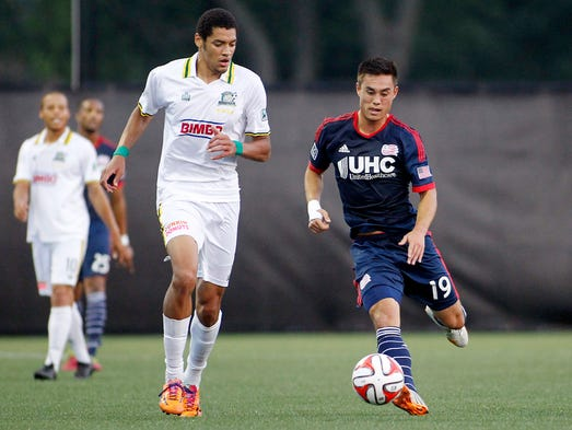 Rochester Rhinos forward Onua Thomas Obasi and New England Revolution midfielder Alec Sundly  battle for the ball during the first half at Stevenson Field.