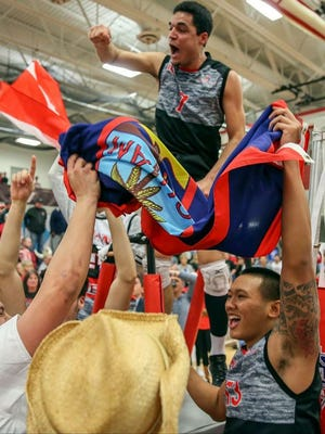 Grand View captain John Chamone celebrates the Vikings' national championship, and Eric Ada hoists the Guam flag  after they beat Benedictine University on April 21.