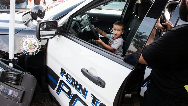 Eli Lawreano, 4, of Nebraska, sits in the driver's seat of a Penn Township police car, Tuesday, August 1, 2017. National Night Out is a community-building campaign that promotes police-community partnerships and neighborhood camaraderie. This was the first year it was held at the Target shopping center, on Wilson Ave.