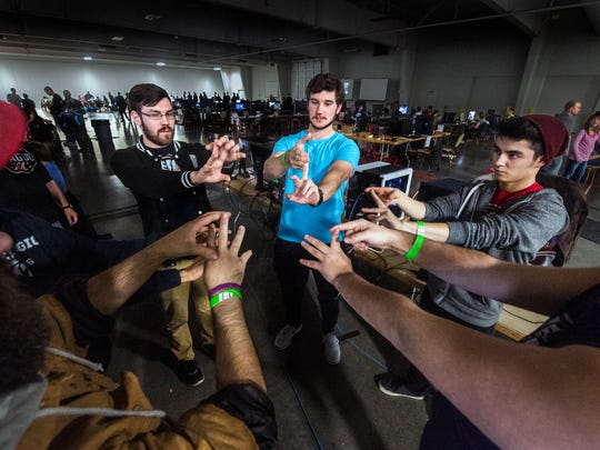 Performance coach Jake Middleton, middle, helps his clients from Team KC, including Mat Smith, left, and Jeremiah Mata, right, on December 4, 2016, during the KC Game On event at the KCI Expo Center in Kansas City, Mo. Team KC is an amateur competitive video gaming group, and Middleton is teaching the team how to exercise for their sport.