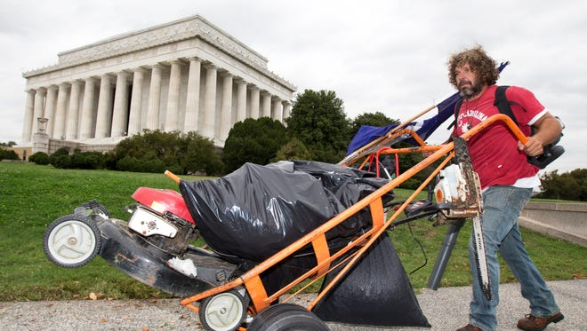 Chris Cox of Mount Pleasant, S.C., pushes a lawn mower near the Lincoln Memorial in Washington, Wednesday.
