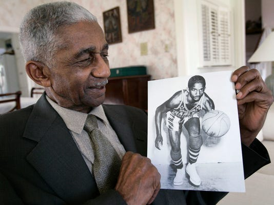 FILE - In this Feb. 14, 2008, file photo, former Harlem Globetrotters great Marques Haynes holds a photo circa 1951 of himself  in his Globetrotters uniform, in Plano, Texas. Haynes died Friday, May 22, 2015, in Plano, Texas. He was 89.  (AP Photo/Tony Gutierrez, File)