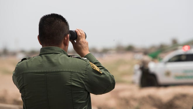 A U.S. Border Patrol agent looks at U.S. Vice President Mike Pence's motorcade at the new replacement wall in Calexico, California on April 30, 2018.