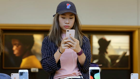 A woman looks at an iPhone 8 Plus at an Apple Store