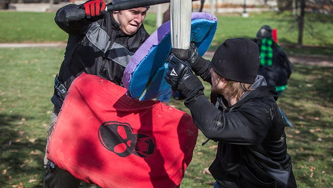 Two people participate in Dagorhir, a medieval-style foam-weapon based fighting game, at an Indiana university.
