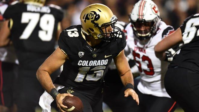 Colorado quarterback Sefo Liufau (13) scrambles with the ball in the first half against Utah.