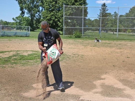 Eric Mack spreads fill dirt on a baseball field in Riverside Park to prepare it for play Wednesday, June 8, 2016.