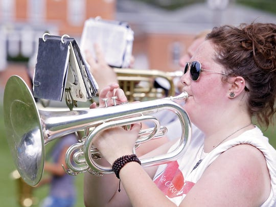 Olivet College band member Emily Cusack plays a mellophone during practice.