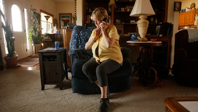 Pam Lee listens to a voice mail message from a scammer on Thursday during an interview at her home in Farmington.
