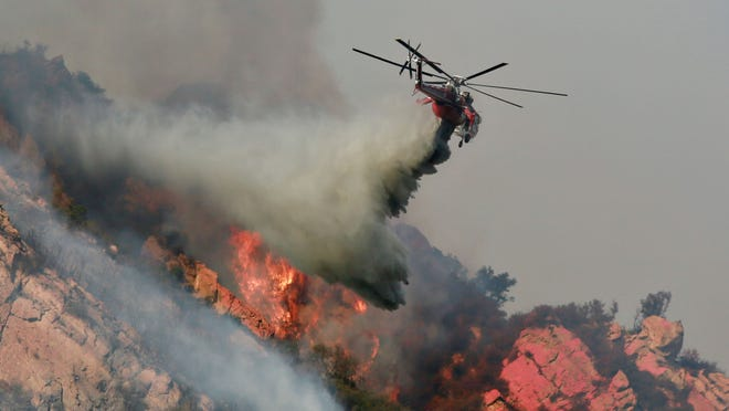 A helicopter drops flame retardant on the Woolsey Fire over Malibu in this Nov. 10 photo. The fire had burned nearly 97,000 acres as of Tuesday.