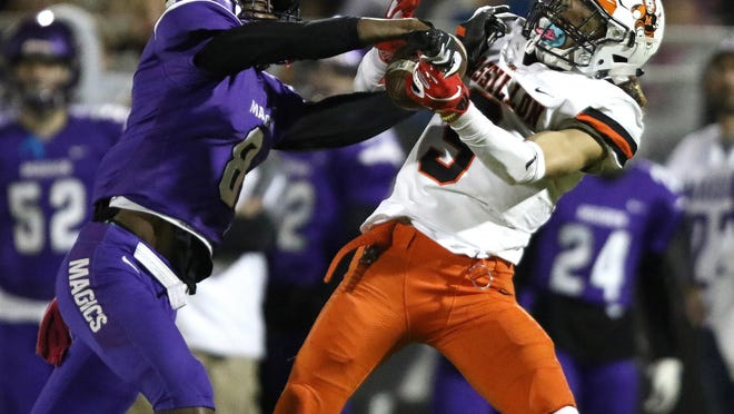 Massillon's Jayden Ballard catches a pass in the first half with pressure from Barberton's Maliq Spragling during a Week 8 Tiger win in 2019.