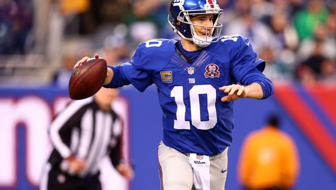 Dec 28, 2014; East Rutherford, NJ, USA; New York Giants quarterback Eli Manning (10) looks to pass against the Philadelphia Eagles during the fourth quarter at MetLife Stadium. The Eagles defeated the Giants 34-26. Mandatory Credit: Brad Penner-USA TODAY Sports