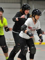 Carrie Hutton, right, and Laura Scudiere, try out roller derby, a skating sport, April 13, in the Marathon Park Ice Arena building in Wausau.