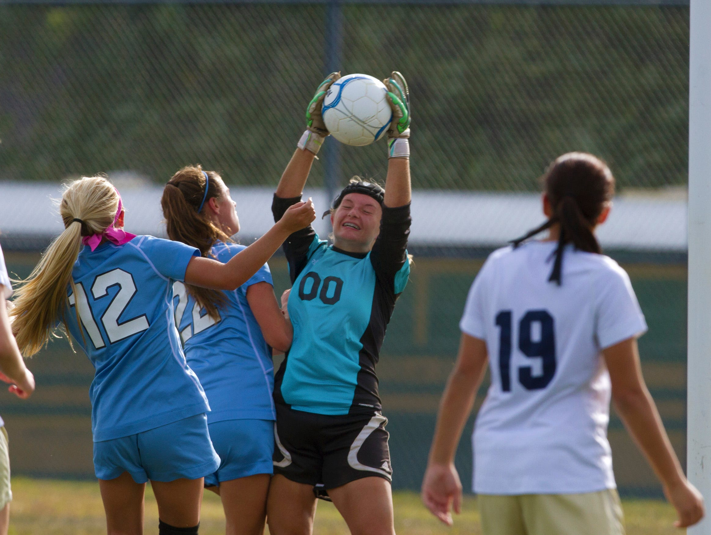 Freehold Township goalie Kaela Chadzuito pulls in a shot on goal as she's crowded by Freehold Boro's Emma Smith and Carly Columbe. Freehold Township Girls Soccer vs Freehold Boro in Freehold Boro on September 25, 2015.