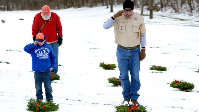 Volunteers place wreaths on graves during the Wreaths Across America ceremony at Indiantown Gap National Cemetery in 2016.