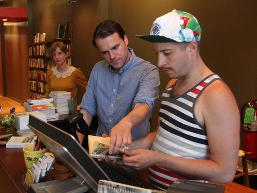 """Jake Herren, right, and co-owner Joshua Arnett look for the price of a copy of """"As I Lay Dying"""" by William Faulkner at Bookmarx on Tuesday, July 1, 2014."""