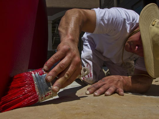 Tito Ocasio, a worker for Stevens Painting, gently glides his paintbrush June 24 on a bowling pin-shaped column at the main entrance of the newly built HeadPinz Fort Myers. The entertainment center is scheduled to open July 16.