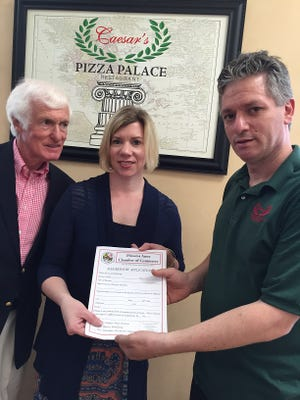 In this May 19, 2016 photo, Princess Anne Chamber of Commerce President Dennis Williams (left), Tammy Zink of Hebron Savings Bank and Michael Halkias, manager at Caesar's Pizza Palace in Princess Anne, announce the pizzeria's new Chamber membership. Halkias' business  joined the local organization of businesses during a  Chamber luncheon, becoming the 75th member and helping the group reach its membership drive goal for the period.