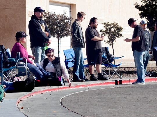 Star Wars fans sit outside the doors of Cineport 10