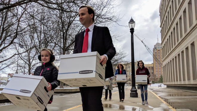 Lt. Gov. Brian Calley and his youngest daughter Karagan (left) and other family members (behind) deliver boxes of petitions to the Secretary of State office in Lansing on Tuesday, April 17, 2018.