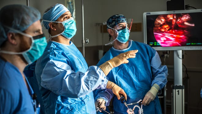Surgeon Peter M. Santoro, M.D., with Surgical Chief Resident Marc Leduc, M.D., performs an operation at Christiana SurgiCenter.