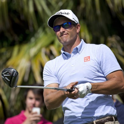 Adam Scott watches his tee shot on the eighth hole during a practice round for the Cadillac Championship golf tournament in Doral, Fla.,