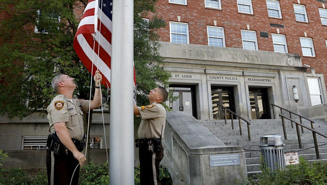 St. Louis County Police police officers Mike Castellano, left, and Sgt. Mike Stoehner lower the flag in front of the county police headquarters to half staff in honor of county police officer Blake Snyder who was shot and killed responding to a call, Thursday, in St. Louis.