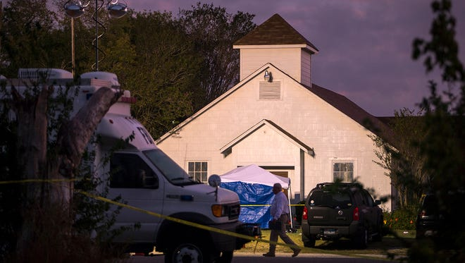 A man walks past the front of the First Baptist Church on where a gunman opened fire during a Sunday service in Sutherland Springs, TX, Nov. 6, 2017.