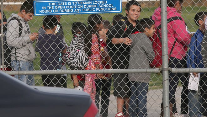 Children at the Orange Center Elementary School in Fresno line up after school near the pipes from the school's well, March 3, 2016.