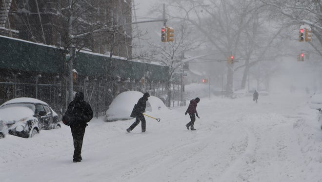 Pedestrians walk in the streets to avoid sidewalks during a snowstorm, Saturday, Jan. 23, 2016, in the Queens borough of New York. Millions of Americans awoke to heavy snow outside their doorsteps as a mammoth winter storm crawled up the East Coast. (AP Photo/Frank Franklin II)