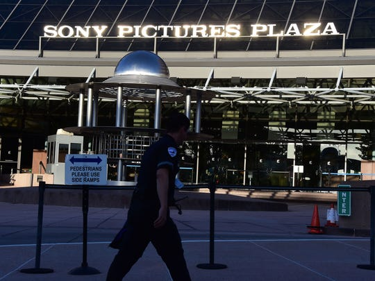 A security guard walks past the entrance to Sony Pictures