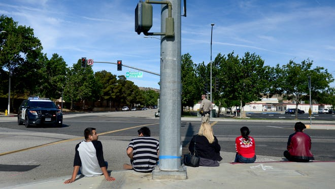 Students wait on a curb outside Highland High School in Palmdale as officers search the school Friday. A high school student was shot in the arm Friday at high school in the California city of Palmdale and a 14-year-old suspect was taken into custody, officials said.