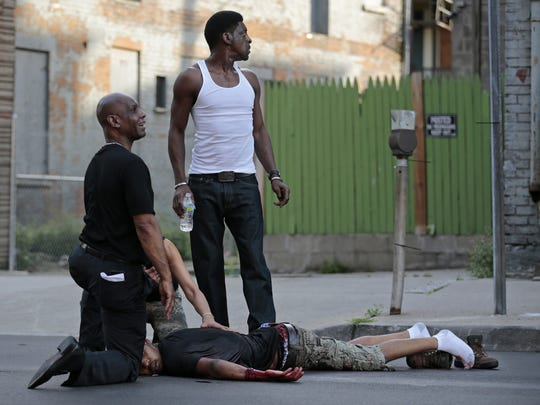 Bishops United and other groups are urging citizens to wear orange Thursday to show their opposition to gun violence. Shown, state Sen. Cecil Thomas, left, tends to a shooting victim near the intersection of Race and Elder Streets last June 22. The shootout occurred near a peace march.