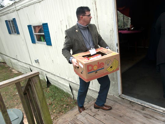 Tim Chandler, from the Panhandle Warrior Partnership, delivers a box of food for a veteran in need days before Christmas.