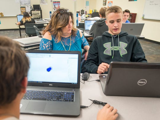 Teacher Michelle Thorpe, left, works with Seth Addington, 17, as he creates a 3D rendering of his car during manufacturing class at Milton High School on Monday, December 4, 2017.  The Santa Rosa County School District would like to create an Innovation High School to prepare students for future work and careers in fields such as cybersecurity, IT, aerospace and engineering.