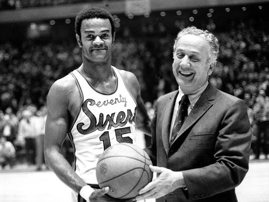 FILE - In this Jan. 29, 1971, file photo, Hal Greer (15), of the Philadelphia 76ers, accepts a ball from Sixers owner Irv Kosloff after Greer reached 20,001 points during a basketball game against the Milwaukee Bucks in Philadelphia, Pa. Greer, a Hall of Fame guard and the 76ers' career leading scorer, has died. The Sixers said Greer died Saturday night, April 14, 2018, in Arizona after a brief illness. He was 81. (AP Photo/File)