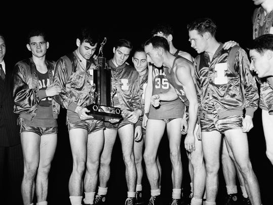 Marvin Huffman, senior guard and captain of the IU basketball team, second from left, looks bashfully at the trophy he received on as his teammates gaze upon it, March 31, 1940, Kansas City, Mo.