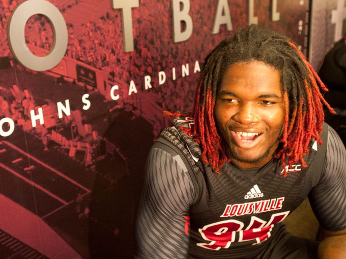 Linebacker Lorenzo Mauldin laughs with reporters as he is interviewed on media day in the press box of Papa John's Cardinal Stadium. 09 August 2014