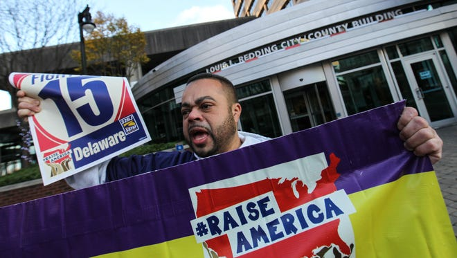 Frank Reyes calls on city and state officials to raise the minimum wage to $15 an hour as workers from the Service Employees International Union Local 32BJ march from the Bank of America building in Wilmington to the Louis L. Redding City County Building on Dec. 3.