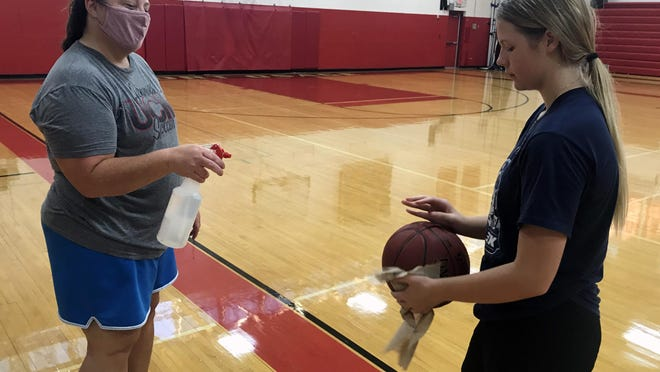 Fort Osage girls basketball coach Lindsay Thompson, left, sanitizes the balls used in practice with freshman Emmah Crowe. The 5-foot-8 forward could play a big role this season for the Indians.
