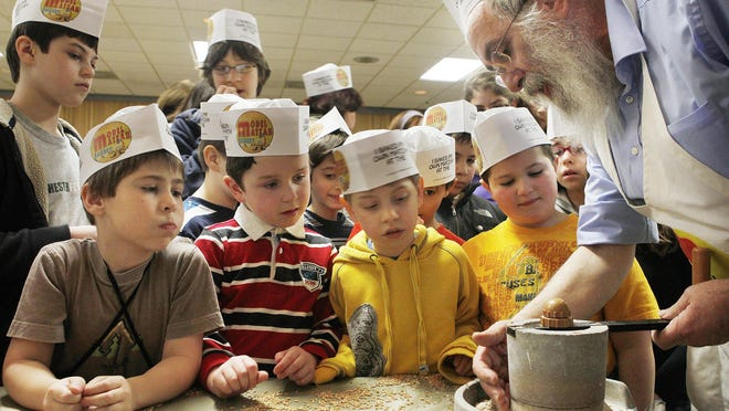 Rabbi Nechemia Vogel, right, demonstrates to a group of eager young Matzah bakers how to grind wheat into flour during the Model Matzah Bakery event at the Jewish Community center in Brighton Sunday, April 3, 2011.