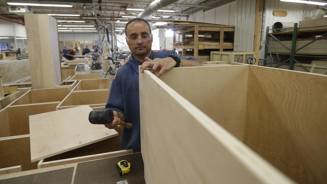 On July 8, inmate William Garrett works on a cabinet at the Habitat for Humanity Prison Build at the Ionia Correctional Facility. Few states have been more aggressive in releasing inmates and diverting offenders than Michigan.