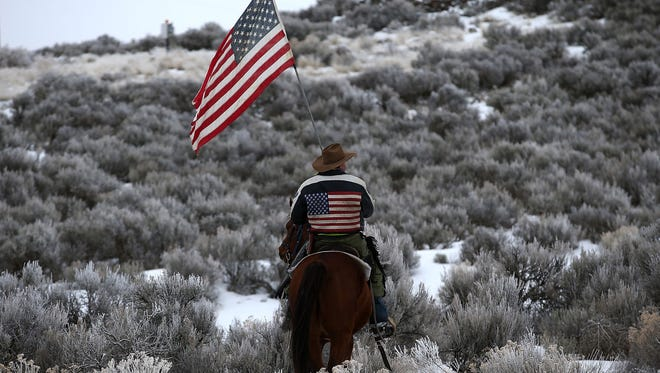 Duane Ehmer carries an American flag as he rides his horse on the Malheur National Wildlife Refuge  on January 7, 2016 near Burns, Oregon.