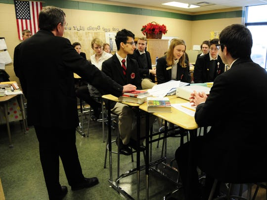 Archbishop Allen Vigneron speaks with students in an English class at Cardinal Mooney High School.