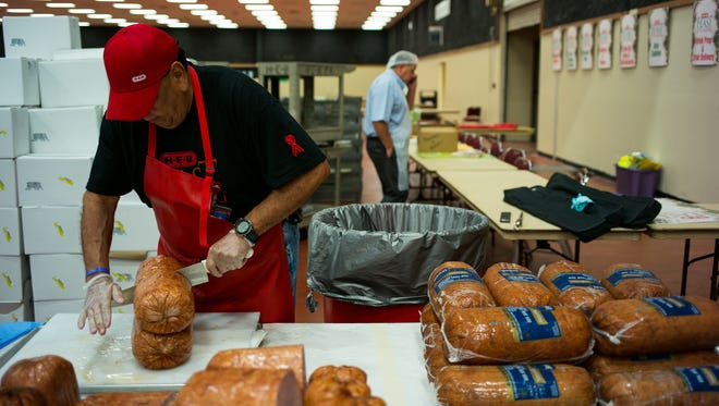 Luis Martinez slices ham's in half Friday morning as they are prepared for HEB's Feast of Sharing at the American Bank Center on Saturday, December 24.