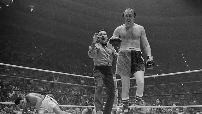 Referee Tony Perez sends Chuck Wepner to a neutral corner after he knocks down heavyweight champion Muhammad Ali in the ninth round of the title bout on March 24, 1975. Ali won with a knockout in the 15th round.