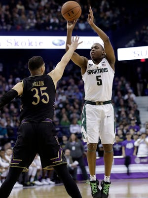 Michigan State guard Cassius Winston, right, shoots over Northwestern guard Aaron Falzon during the first half of an NCAA college basketball game Saturday, Feb. 17, 2018, in Rosemont, Ill.