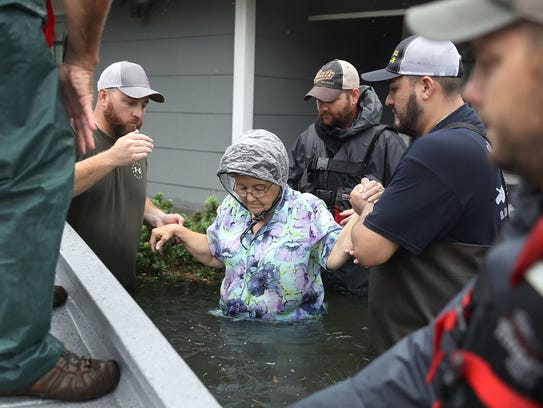 Volunteer rescue workers help a woman from her home