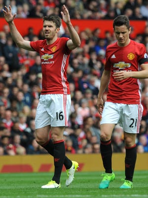Manchester United's Michael Carrick (L) and Manchester United's Ander Herrera react during the English Premier League soccer match between Manchester United and Swansea City at Old Trafford stadium.