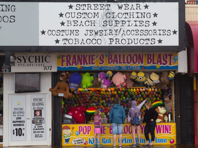 Shore visitors try to decide whether to try their luck a Frankie's Balloon Blast booth in Seaside Heights. People still visit Seaside Heights boardwalk Saturday in spite of steady rain the came down most of the morning.  Seaside Heights on August 2, 2014 - Peter Ackerman / Staff Photographer